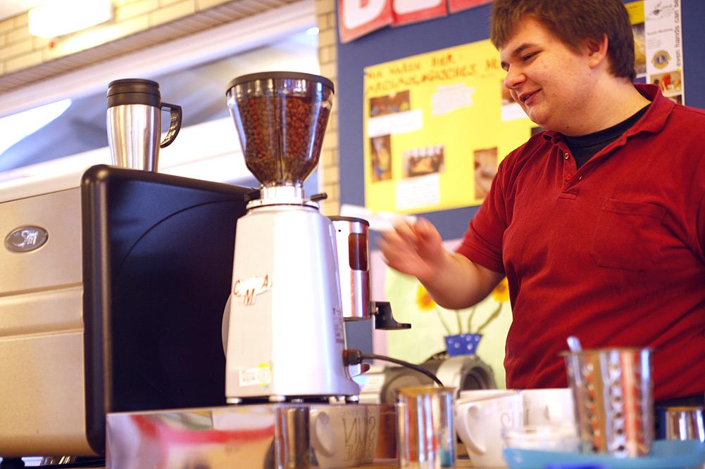 Ein Schüler arbeitet an einer professionellen Espressomaschine, er lächelt.