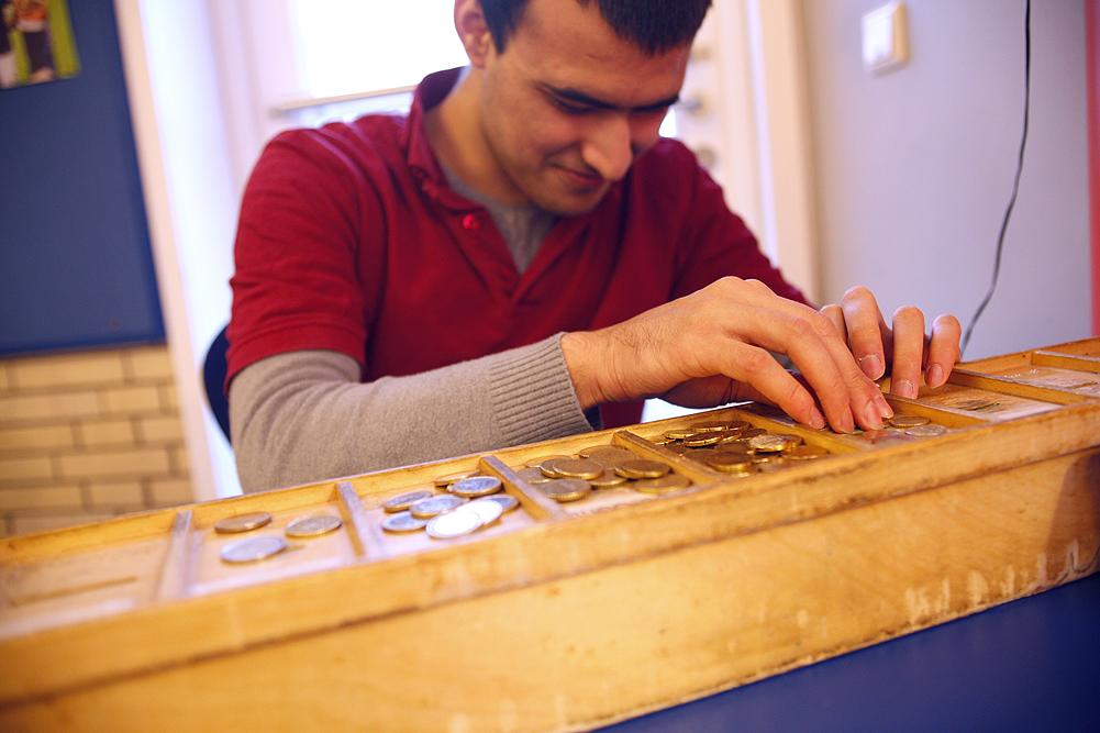 Ein blinder Schüler kassiert und ertastet die unterschiedlichen Münzen.