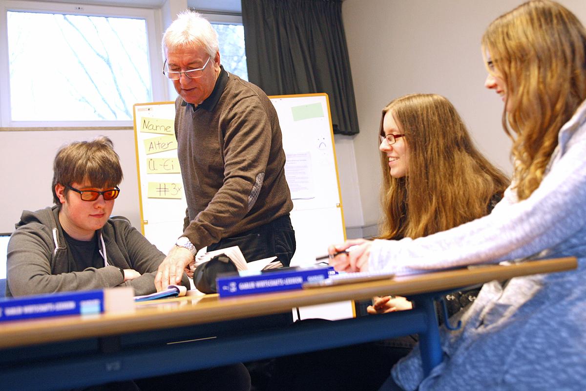 Ein Schüler sitzt mit zwei Mitschülerinnen an einem Tisch. Ein Lehrer deutet auf das Blatt des Schülers und erklärt etwas.