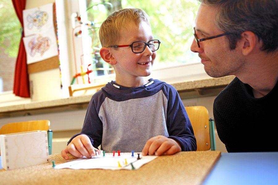 Ein Schüler arbeitet mit einem Lehrer an einer Korkplatte. Beide lächeln sich an.
