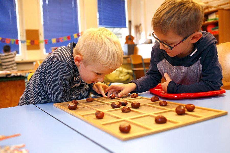 Zwei Schüler spielen an einem tastbaren Spielbrett mit Kastanien.