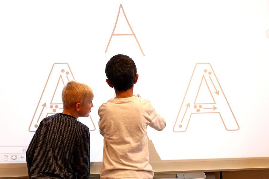 """Zwei Schüler vor einem interaktiven Whiteboard, auf dem sie das Schreiben des Buchstabens """"A"""" üben."""