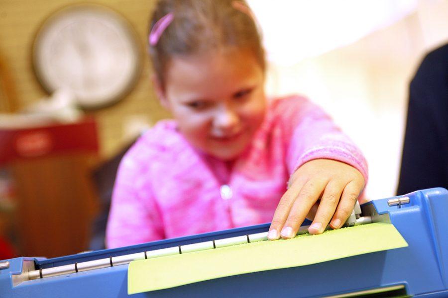 Eine Schülerin arbeitet an einer Punktschriftmaschine.