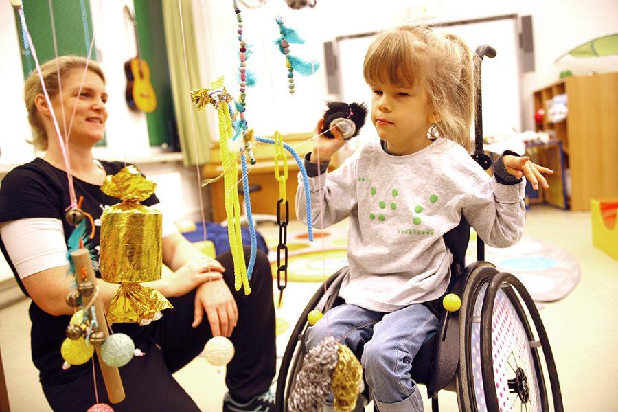 Eine Schülerin im Rollstuhl und eine Lehrerin in einer Fördersituation