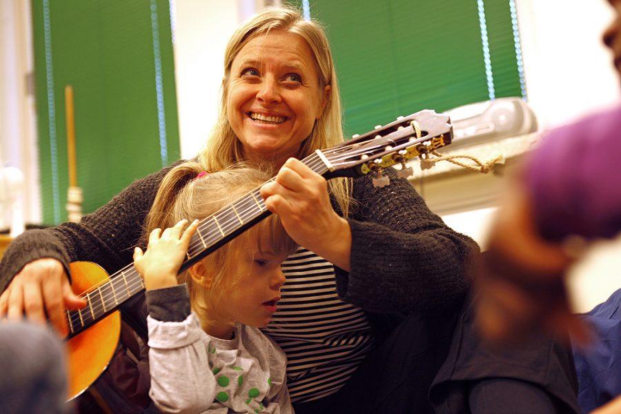 Eine Lehrerin spielt Gitarre, eine Schülerin sitzt vor ihr und ertastet das Griffbrett der Gitarre.