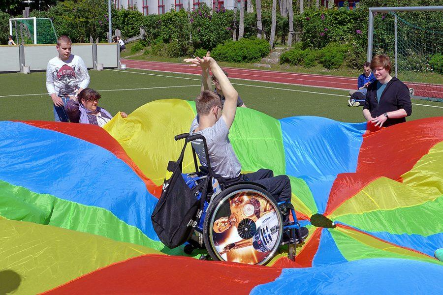 Unterrichtssituation auf dem Sportplatz, bei der ein Schüler im Rollstuhl auf einem großen bunten Schwungtuch steht, das von seinen Mitschülern gehalten wird.