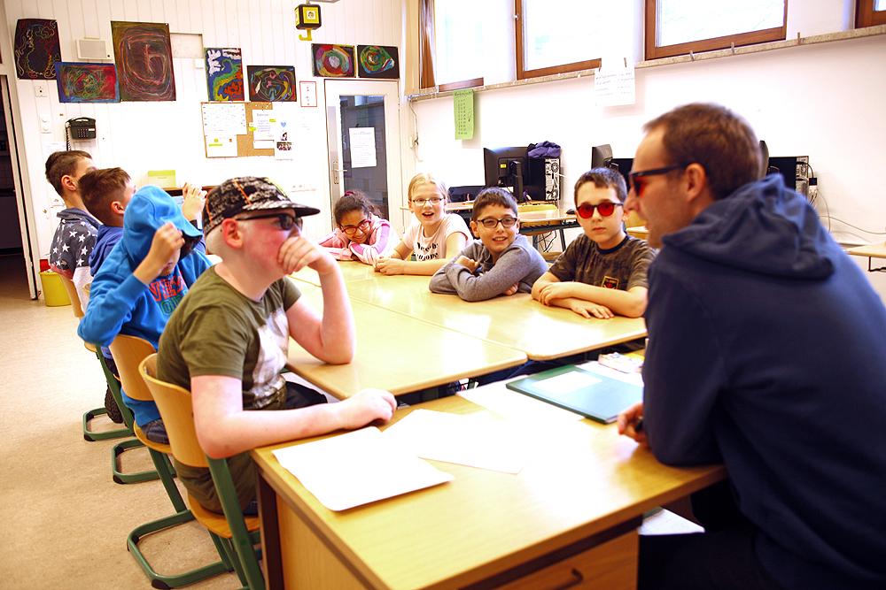 Ein Lehrer und eine Gruppe von acht Schülern der Stadtteilschule sitzen an einem Gruppentisch.