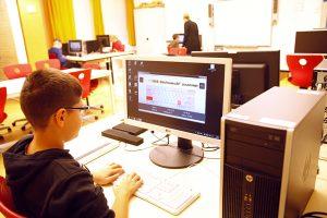 Ein Schüler sitzt vor einem PC-Monitor und übt das Zehnfingersystem mithilfe einer Software.