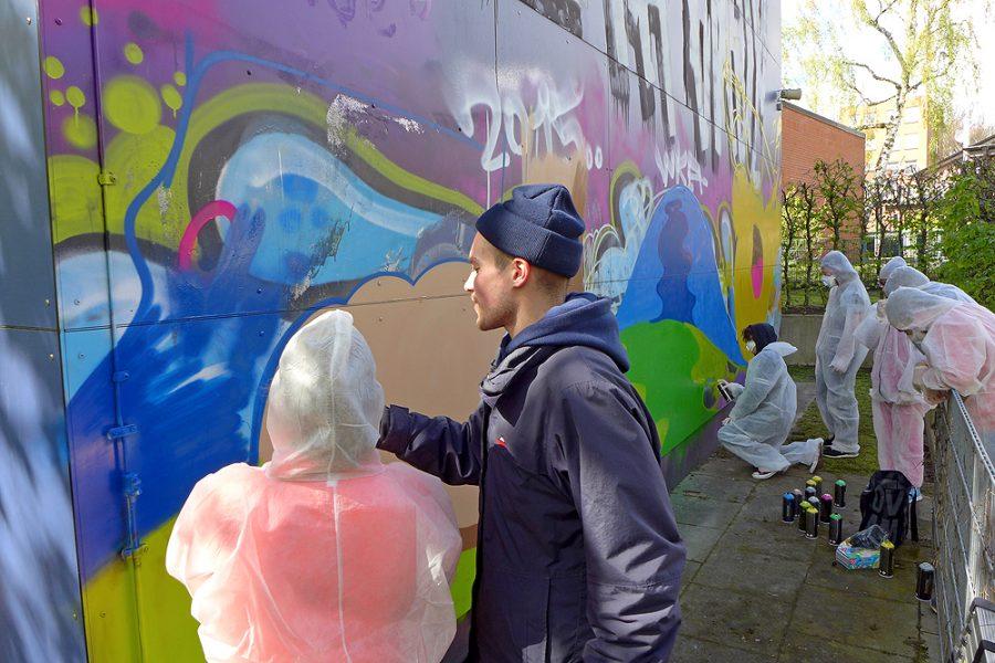 Eine Gruppe von Schülern besprüht mit einem Graffiti-Künstler zusammen eine Wand.