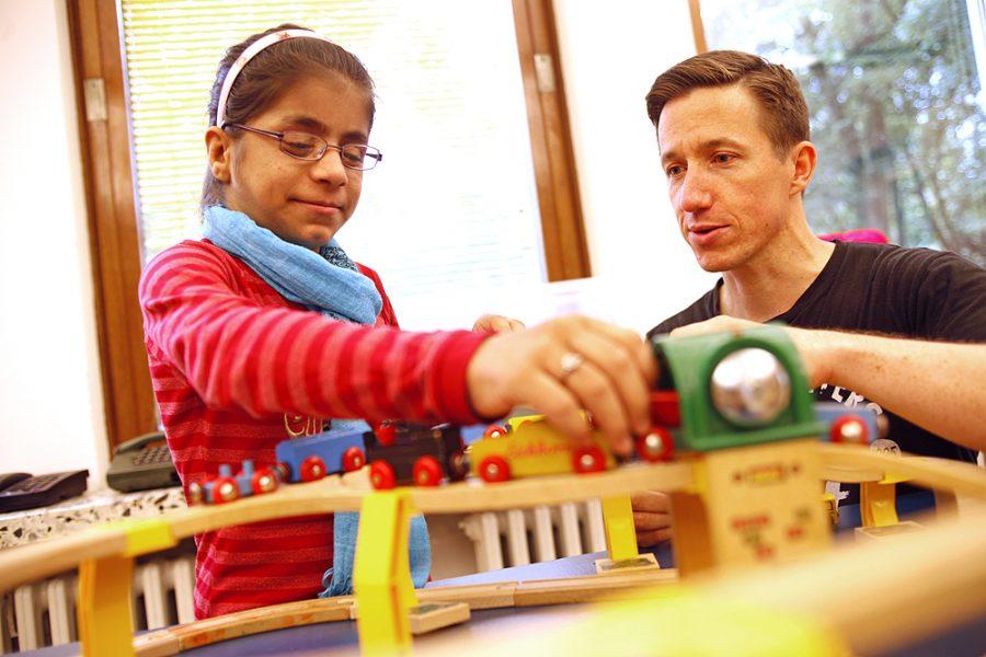 Ein Erzieher und eine Schülerin spielen mit einer Holzeisenbahn.
