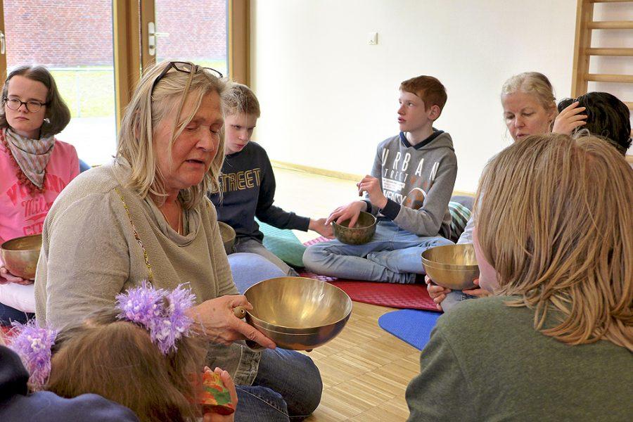 Eine Lerngruppe und zwei Lehrerinnen im Sitzkreis auf dem Fußboden. Jeder hat eine Klangschale.