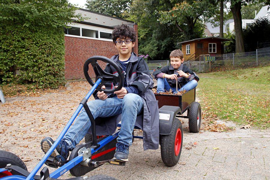 Ein Schüler fährt ein Kettcar mit Anhänger, darin sitzt ein Mitschüler.