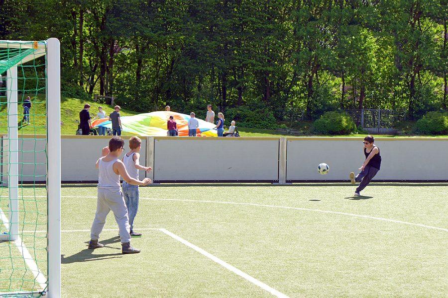 Drei Schüler spielen Fußball.