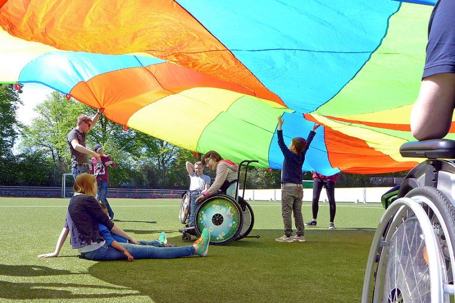 Eine Lerngruppe mit einem Schwungtuch auf dem Sportplatz des BZBS