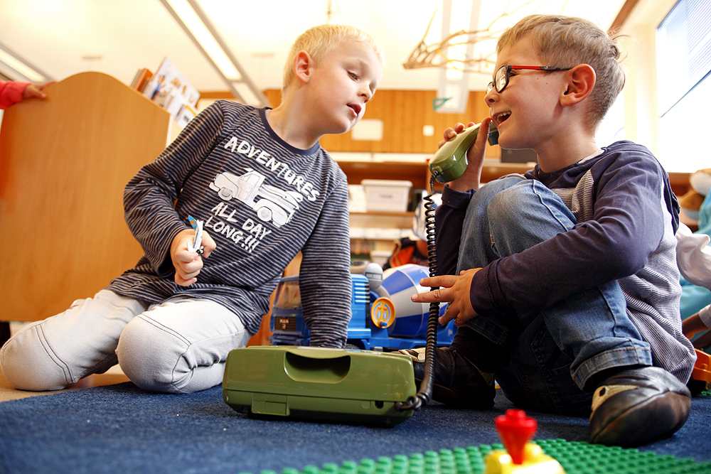 Zwei Schüler spielen mit einem alten kabelgebundenen Telefon.