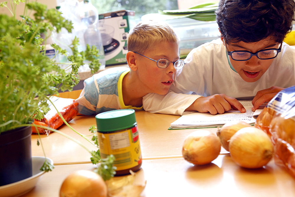 Zwei Grundschüler sitzen an einem Tisch und lesen gemeinsam ein Rezept. Vor ihnen auf dem Tisch sind Kartoffeln, Zwiebeln, Brühe und Petersilie.