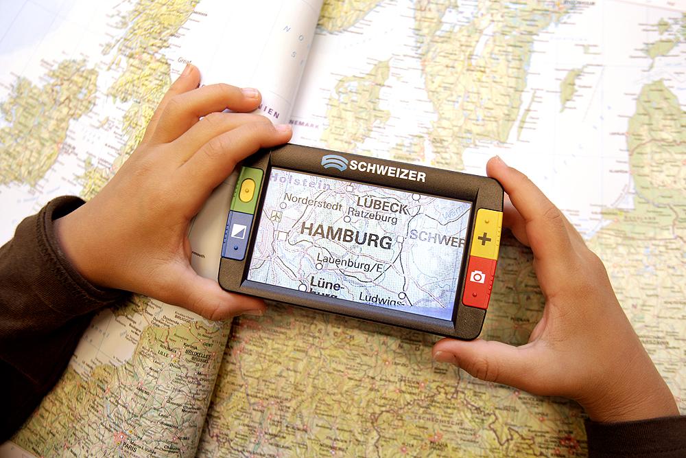 Eine Landkarte wird mithilfe einer elektronischen Lupe vergrößert. Im vergrößerten Ausschnitt erkennt man die Stadt Hamburg.
