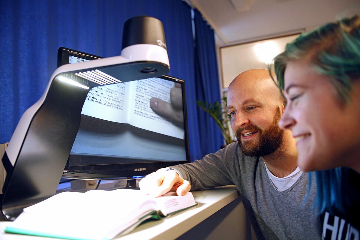 Ein Lehrer zeigt mithilfe eines Bildschirmlesegerätes einer Schülerin etwas in einem Wörterbuch.