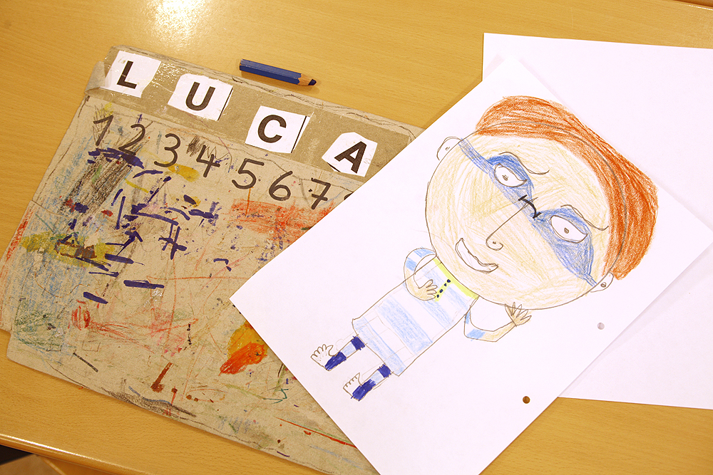 """Ein Schülerarbeitsplatz mit einer Unterlage, auf der in großen Buchstaben der Name """"Luca"""" steht. Daneben liegt ein blauer Buntstift. Schräg auf der Unterlage liegt ein mit Buntstiften gemaltes Bild von einem rothaarigen Jungen mit blauer Maske."""