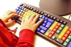 Eine Tastatur zum Erlernen des Zehnfinger-Systems. Die Tasten, die mit dem gleichen Finger betätigt werden, sind jeweils mit einer Farbe gekennzeichnet.