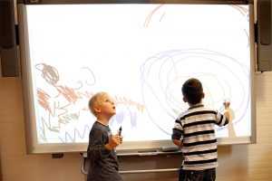 Zwei Grundschüler an einem interaktiven Whiteboard, der eine malt, der andere hält einen Stift in der Hand und schaut nach oben zum Beamer.