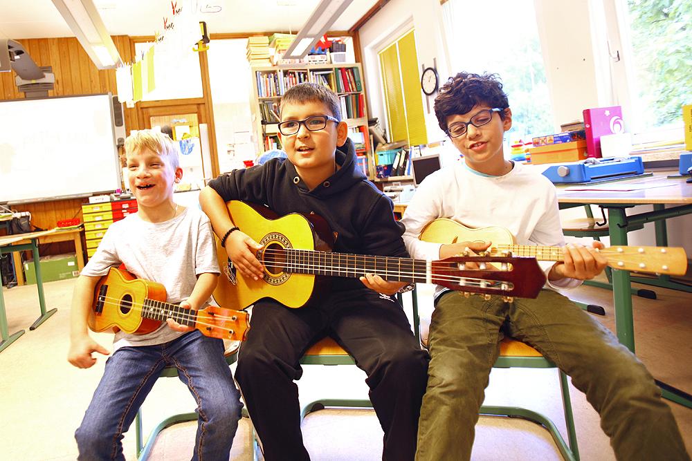 Drei Grundschüler sitzen nebeneinander auf Stühlen. Zwei haben eine Ukulele, der dritte eine Gitarre.