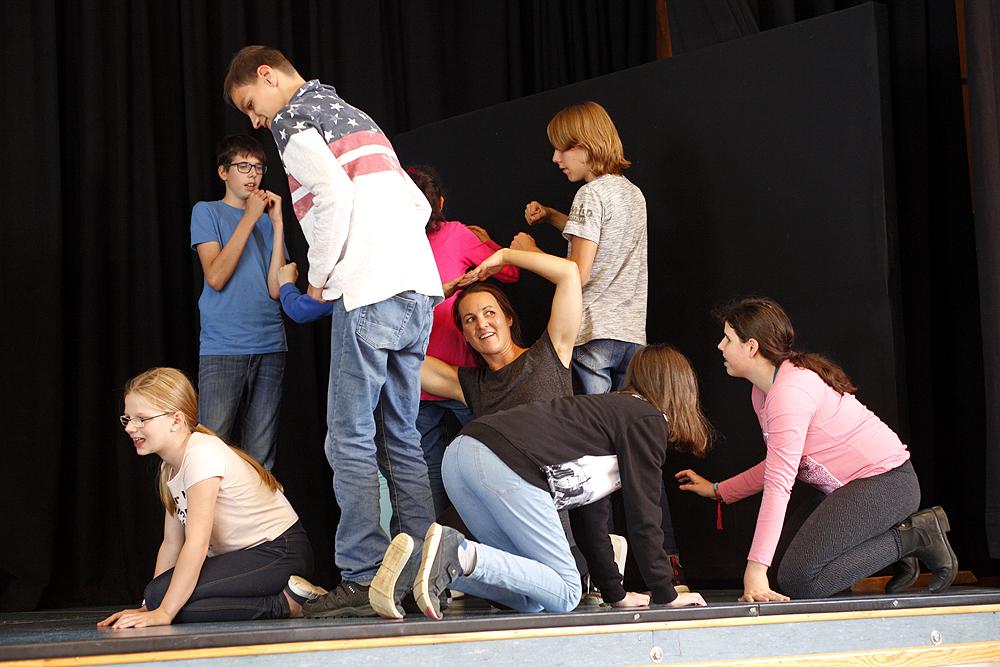 Eine Gruppe von sieben Schülerinnen und Schülern mit einer Lehrerin bei einer Theaterprobe auf der Bühne.