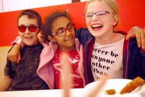 Ein Schüler und zwei Schülerinnen sitzen nebeneinander, haben die Arme gegenseitig auf die Schultern gelegt und lachen.