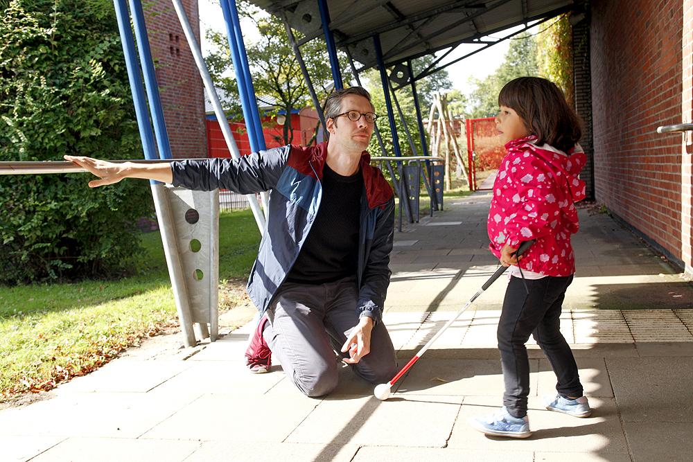 Ein Pädagoge zeigt einem blinden Mädchen das Geländer-Leitsystem im Außenbereich.
