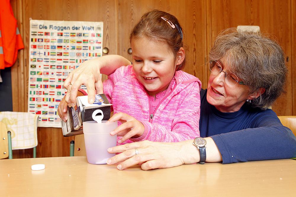 Eine Lehrerin zeigt einer Grundschülerin eine Technik zum Einschenken von Getränken in ein Glas.