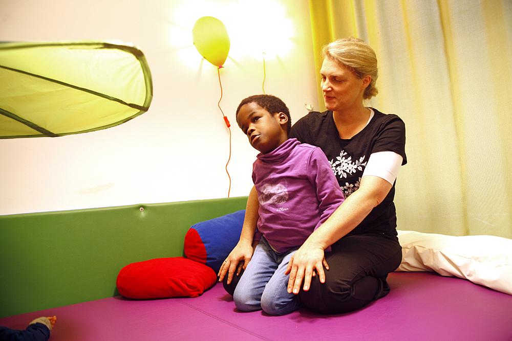 Eine Therapeutin und ein Schüler bei einer Übung im Sitzen.