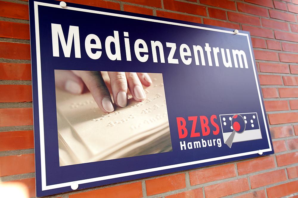 Schild des Medienzentrums mit Schriftzug und einem Bild von einer tastenden Hand in einem Punktschrifttext.