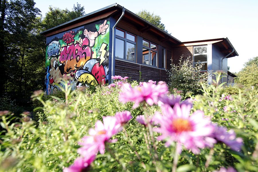 Schulgebäude mit Holzverkleidung, eine Wand ist mit bunten Graffitis verziert.