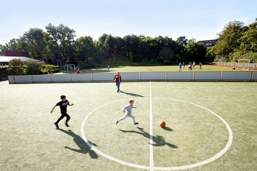 Mehrere Schüler spielen Fußball auf dem Blindenfußballplatz mit Seitenwänden.
