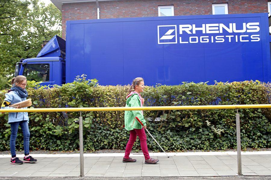 Zwei Schülerinnen auf dem Fußweg in der Einfahrt der Schule. Sie kommen vom Einkaufen.