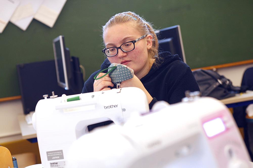 Eine Schülerin sitzt an einer Nähmaschine und betrachtet ihr Arbeitsergebnis.