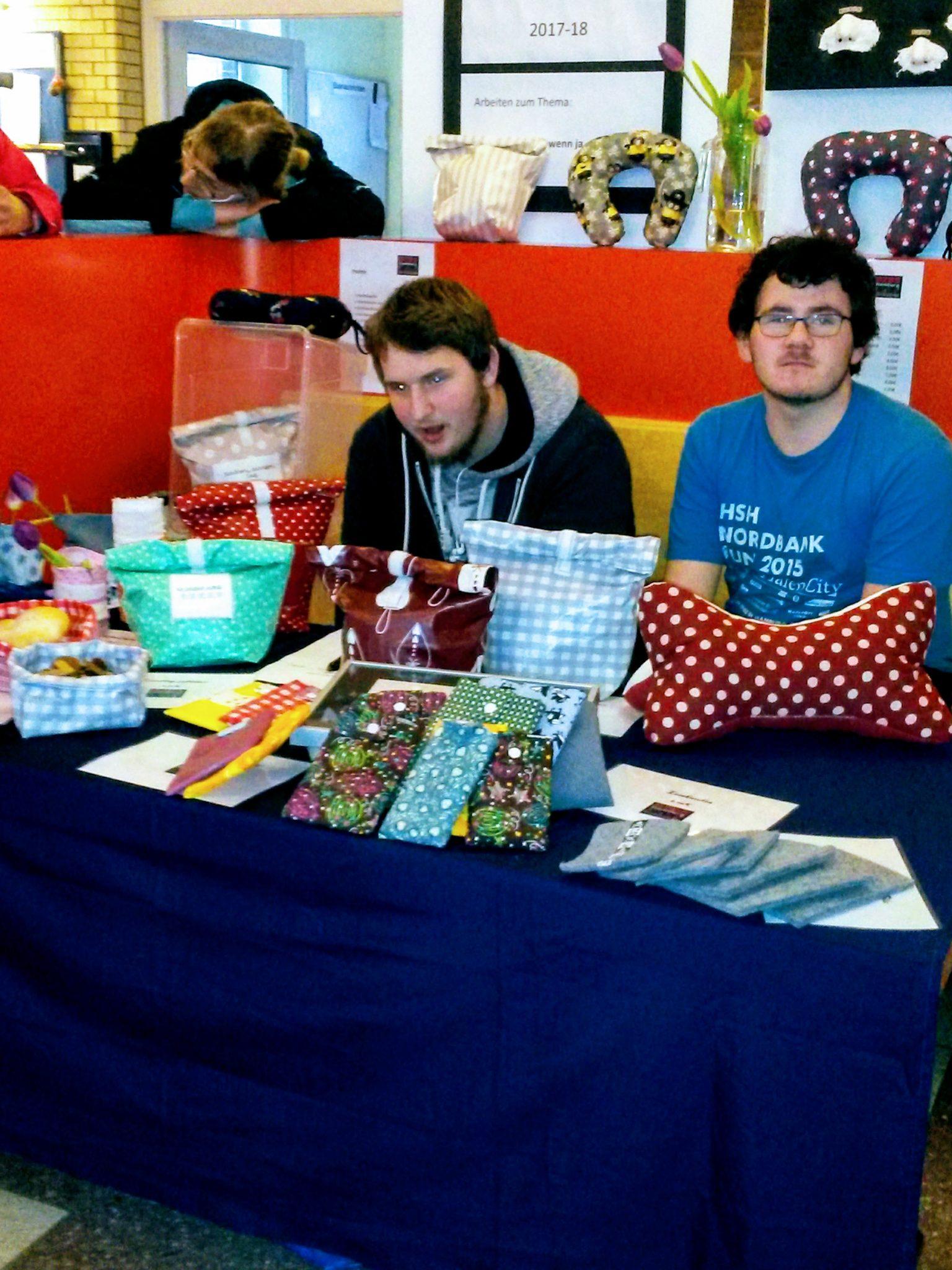 Zwei Schüler des BVJ bieten selbst genähte Taschen zum Verkauf an.